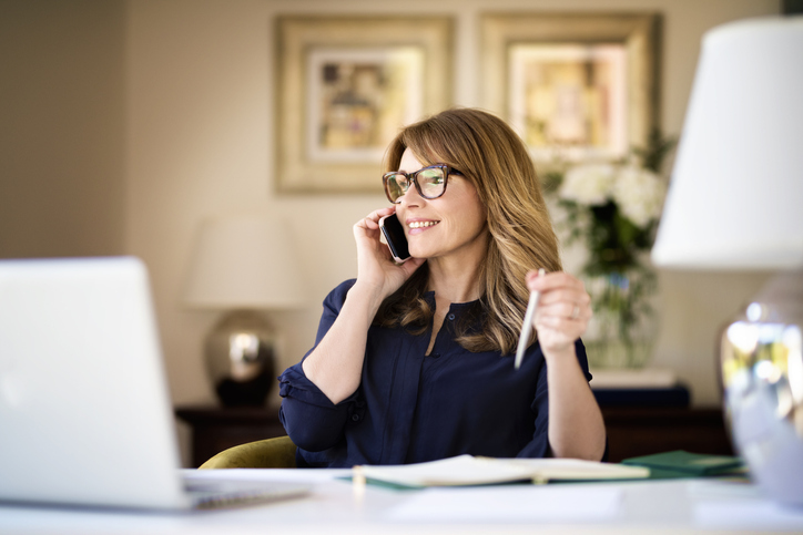 Happy businesswoman using mobile and laptop while working at home